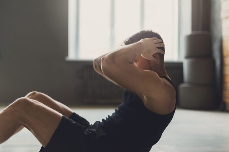 Young man fitness workout, sit-up crunches for abs. Training indoors