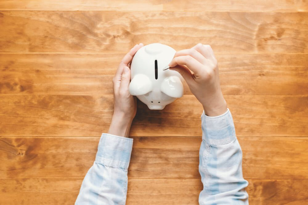 Woman holding a white piggy bank on a wooden desk