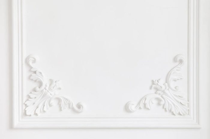 The white wall is decorated with exquisite elements of plaster moldings