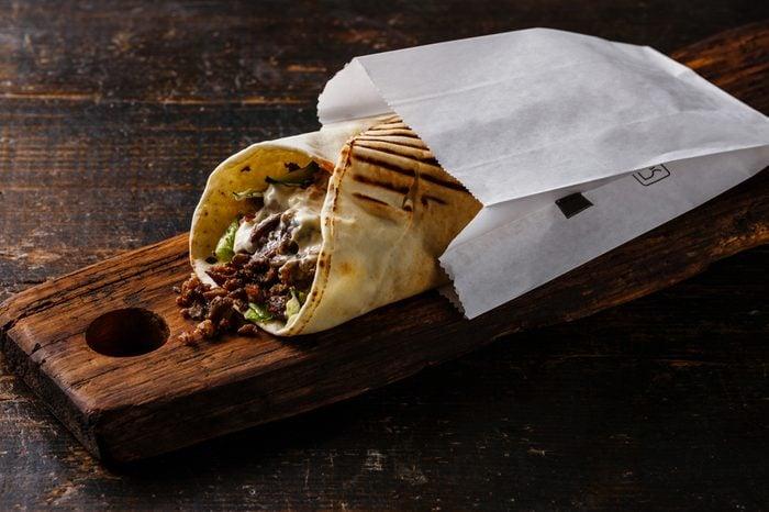 Doner Kebab Gyros Shawarma beef roll in pitta bread Wrap sandwich on wooden background
