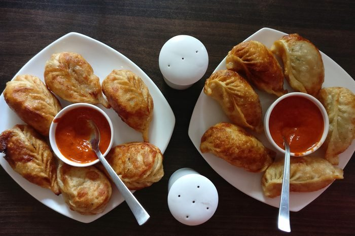 Veg fried cheese momos with sauce in white plates on a wooden table.
