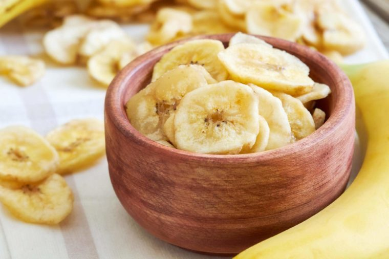 Homemade banana chips (dried and fried banana slices) in wooden bowl