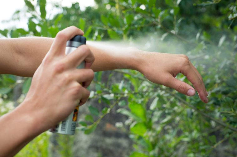 Young man spraying mosquito / insect repellent in the forrest, insect protection