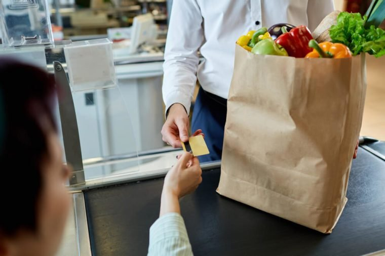 The man's hand buyer pays by card for purchase in paper bag with healthy fresh meal near cashier at the supermarket during shopping