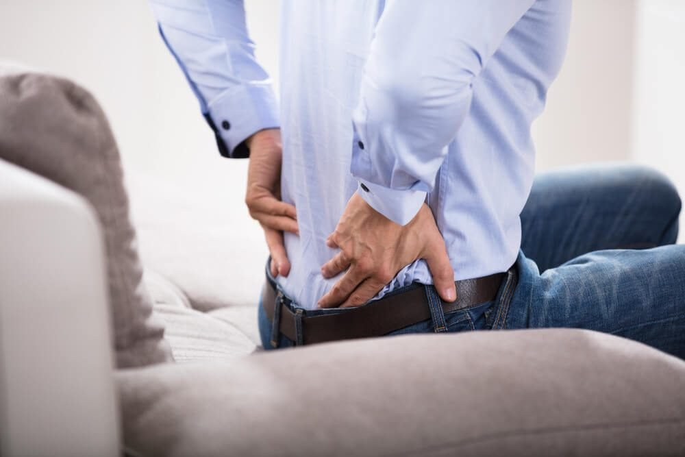Close-up Of A Person Sitting On Sofa Suffering From Backache At Home