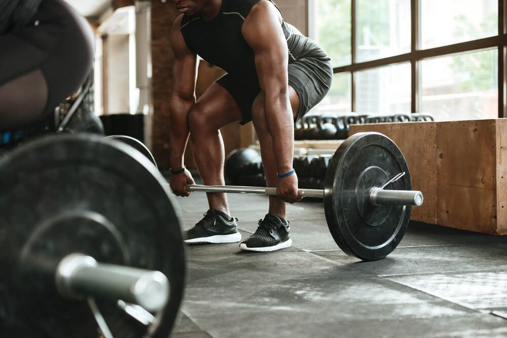 Cropped image of a young african sportsman lifting a barbell at the gym