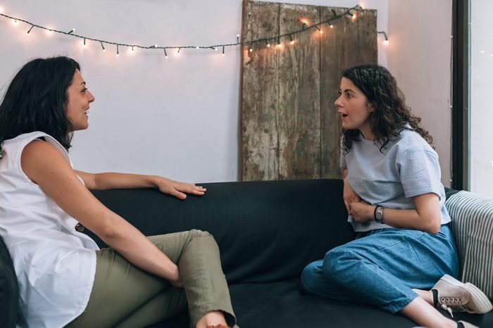 Two women friends talking to each other on a couch in apartment