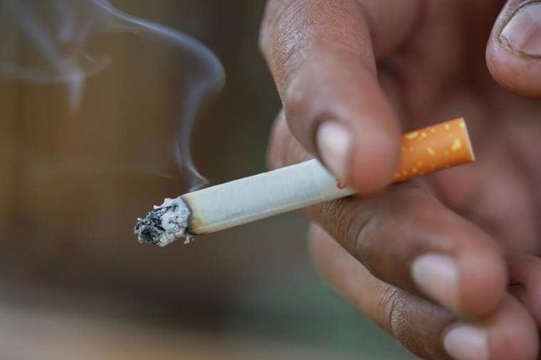 Close up man hand smoking cigarette.