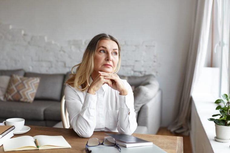 Attractive blonde mature female writer sitting at desk at home placing chin on her hands and looking away with thoughtful or unhappy expression while experiencing writer's block and creative slowdown