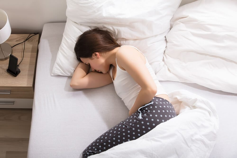 Elevated View Of A Woman Lying On Bed Having Stomach Pain