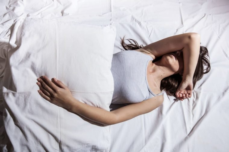 Young woman with insomnia cover her face with hand in bed