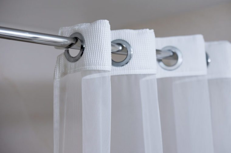 Shower curtain hanging from a chrome shower curtain rod