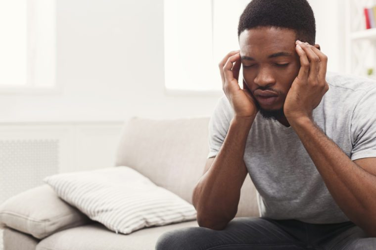 Young african-american businessman suffering from headache after hard working day, sitting on couch at home, copy space