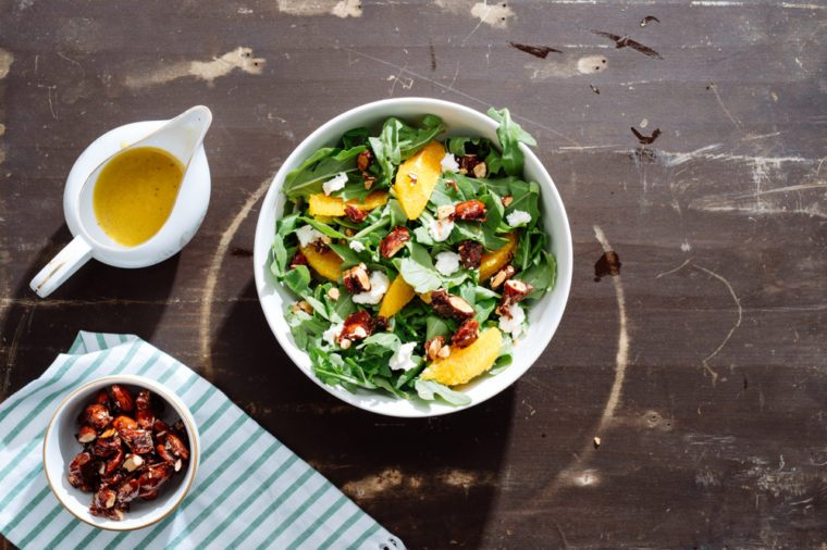 Overhead of an orange and arugula salad with orange segments, candied nuts, ricotta cheese and orange vinaigrette on dark brown surface with nuts in a bowl.