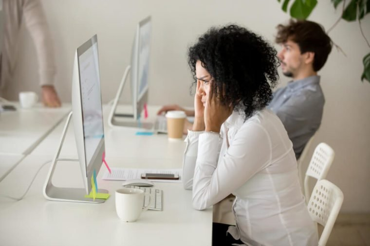 Stressed young african american businesswoman suffering from headache migraine touching temples at workplace, frustrated black woman employee tired from computer work can not concentrate or focus