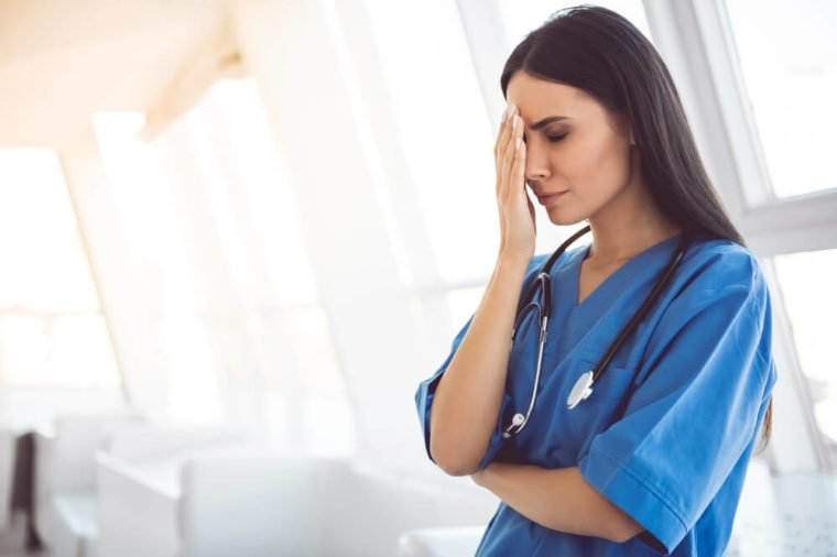 Beautiful doctor in blue scrubs is covering her face while standing in hospital corridor