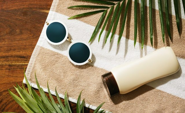 Different items for beach vacations. Sunscreen, sunglasses and pineapple fruit