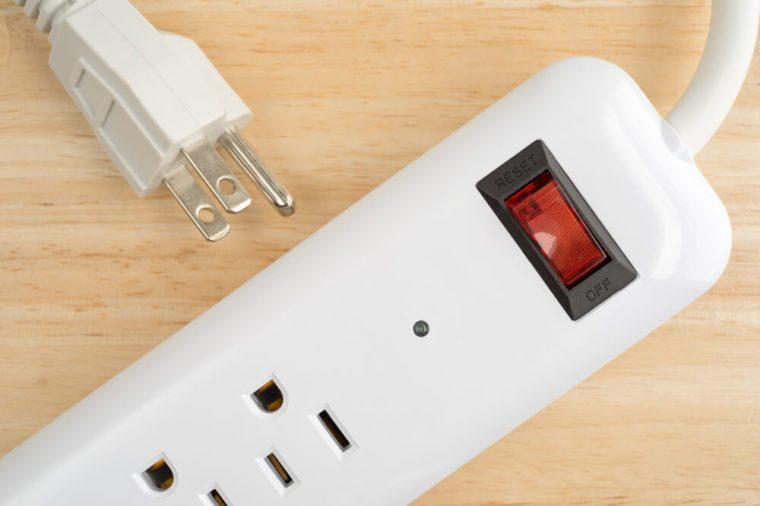 Top close view of a household surge protector on a wood table top.
