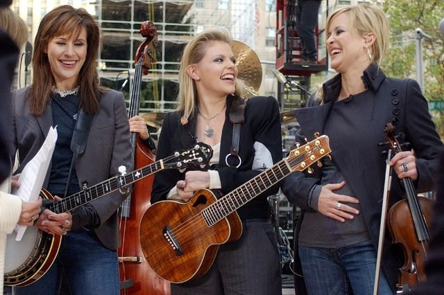 "The Dixie Chicks' Martie Maguire, right, holds her stomach as she was ask about her pregnancy as she appeared with bandmates Emily Robison, left, and Natalie Maines during the NBC ""Today"" concert series in New York's Rockefeller Plaza, . Maguire's baby is due in May"