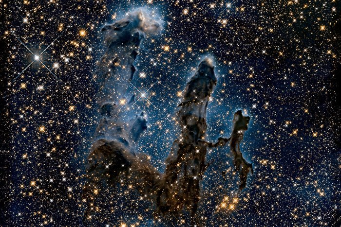 This NASA Hubble Space Telescope image, taken in near-infrared light, transforms the pillars into eerie, wispy silhouettes, which are seen against a background of myriad stars. The near-infrared light can penetrate much of the gas and dust, revealing stars behind the nebula as well as hidden away inside the pillars. Some of the gas and dust clouds are so dense that even the near-infrared light cannot penetrate them. New stars embedded in the tops of the pillars, however, are apparent as bright sources that are unseen in the visible image. The ghostly bluish haze around the dense edges of the pillars is material getting heated up by the intense ultraviolet radiation from a cluster of young, massive stars and evaporating away into space. The stellar grouping is above the pillars and cannot be seen in the image. At the top edge of the left-hand pillar, a gaseous fragment has been heated up and is flying away from the structure, underscoring the violent nature of star-forming regions. Astronomers used filters that isolate the light from newly formed stars, which are invisible in the visible-light image. At these wavelengths, astronomers are seeing through the pillars and even through the back wall of the nebula cavity and can see the next generations of stars just as they're starting to emerge from their formative nursery.