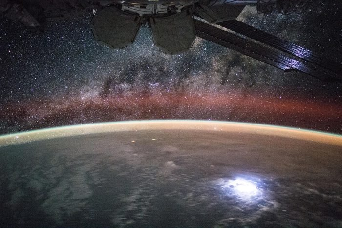 """View (part of a time lapse sequence) of stars in the Milky Way Galaxy visible over an Earth limb as seen by the Expedition 44 crew. Astronaut Kjell Lindgren captured a lightning strike from space so bright that it lights up the space station's solar panels. He posted this on Twitter and Instagram on Sept. 2 saying """"Large lightning strike on Earth lights up or solar panels."""""""