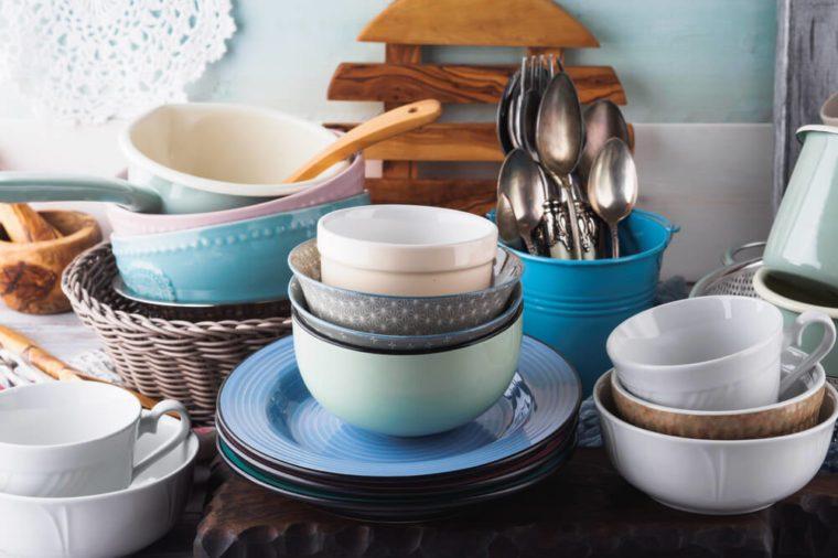 Ceramic and enamel crockery tableware on wooden background. Pastel vintage colors