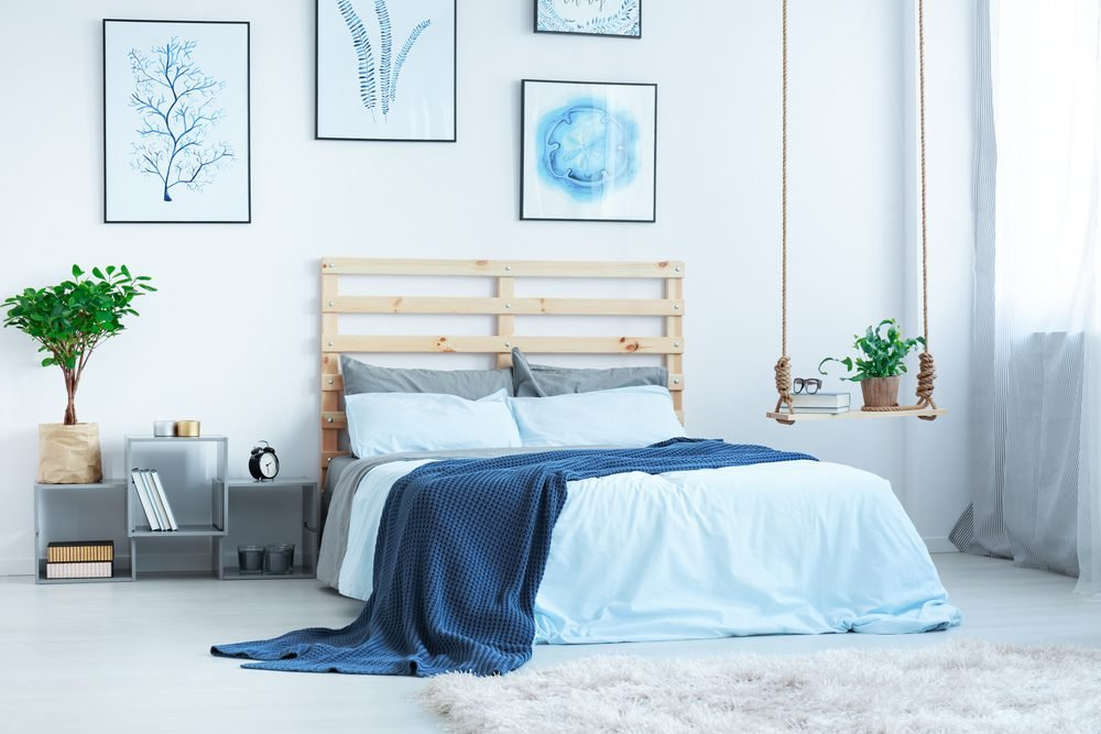 Modern bedroom with double bed, posters and plants