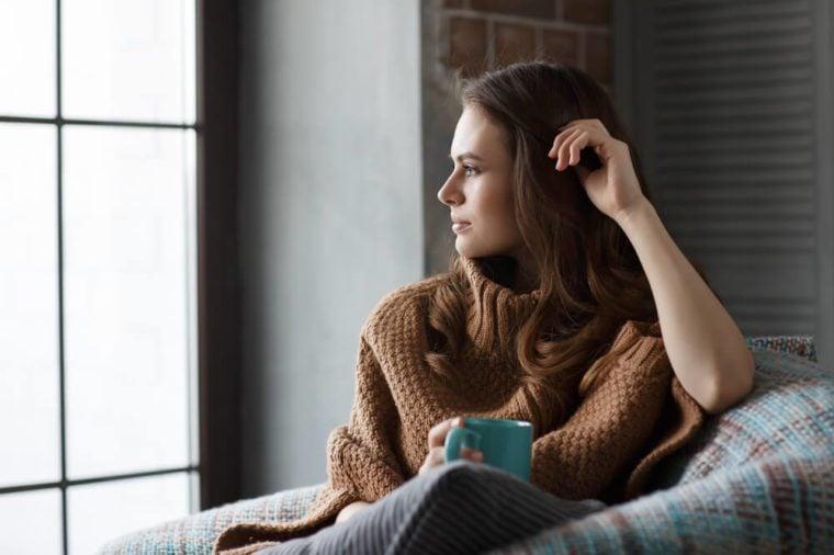 Beautiful girl sitting in an armchair with a mug of coffee looking in window. Thoughtful look
