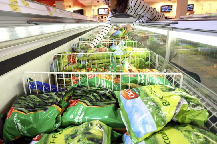 MODEL RELEASED Woman purchasing frozen vegetables in the frozen food section of a self-service grocery department, supermarket, Germany