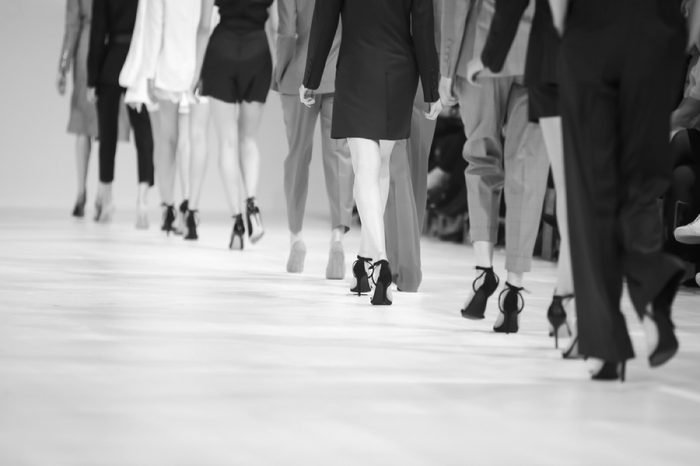 Fashion Show, Catwalk Runway Show Event. Detail of lined up rear view fashion models legs with high heels.