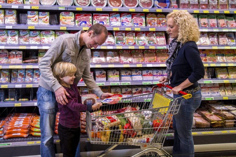 MODEL RELEASED Family shopping with a shopping trolley in the packed meat department of a supermarket, Germany