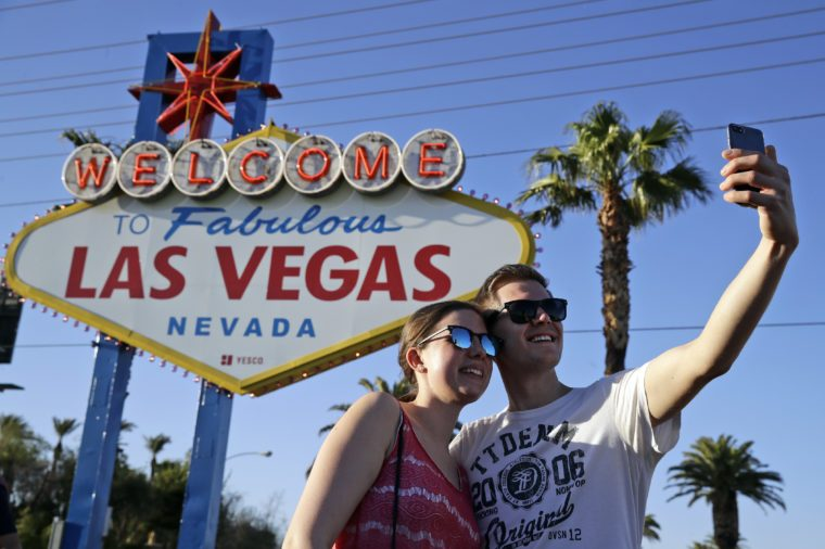 Tourists pose for photos in front of the Welcome to Las Vegas sign that has flowers honoring the people who died in a mass shooting on Sunday in Las Vegas on . A gunman opened fire on an outdoor music concert on Sunday making it the deadliest mass shooting in modern U.S. history. But even though the city is in mourning, for many it is business as usual with celebrations and parties continuing