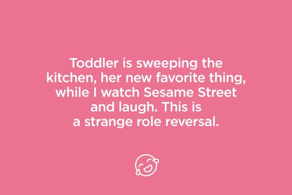 toddler is sweeping the kitchen