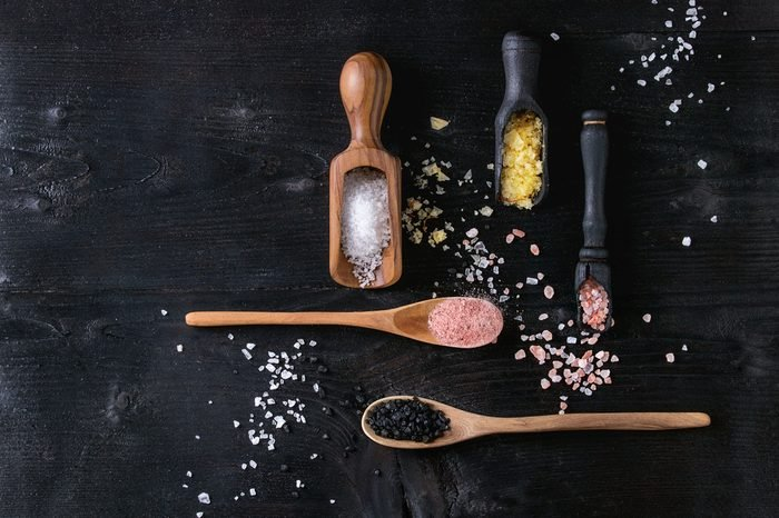 Variety of different colorful salt yellow saffron, pink, black himalayan, white sea and fleur de sel in wooden spoons over black burned wood background. Top view with space