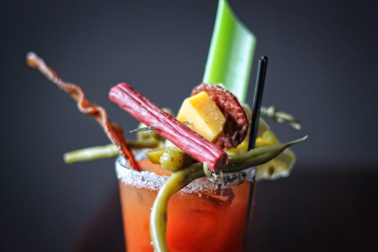 Close up Bloody Mary cocktail with tomato juice plus bacon, pickle, celery, jerky, and olive garnish