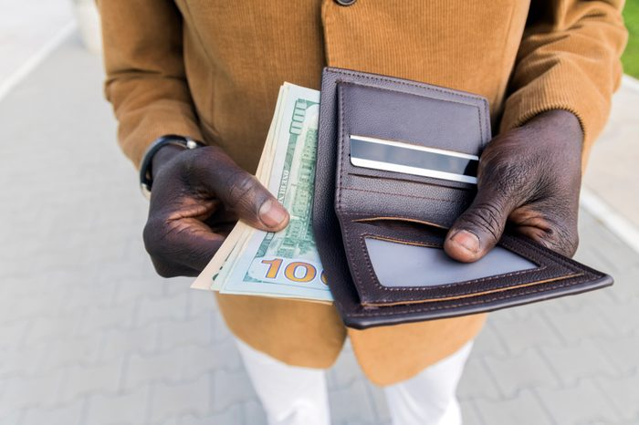 Cropped shot of African-American businessman gets money from the wallet. Purse with dollars in their hands. Businessman's hand in suit takes out dollar money from a wallet