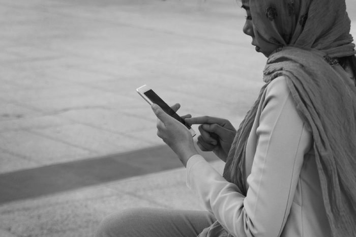 Arab businesswoman messaging on a mobile phone in the city