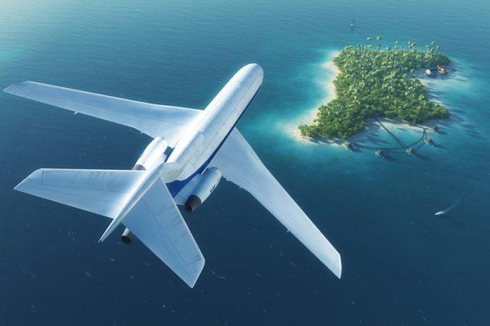 Large passenger plane flies over paradise tropical island