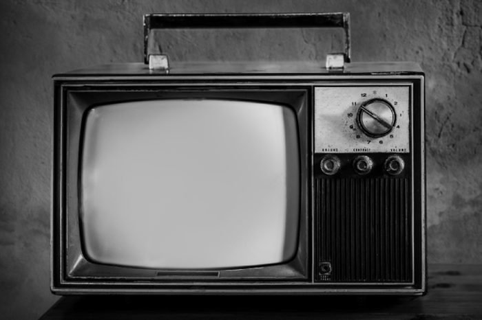 Vintage, Old television on a wooden table with old wall background,Retro TV technology filter effect
