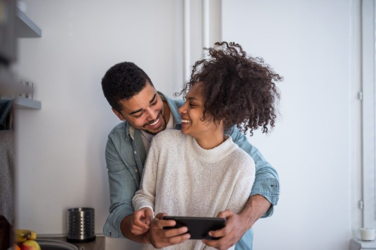 Happy african american couple using a tablet in the kitchen.
