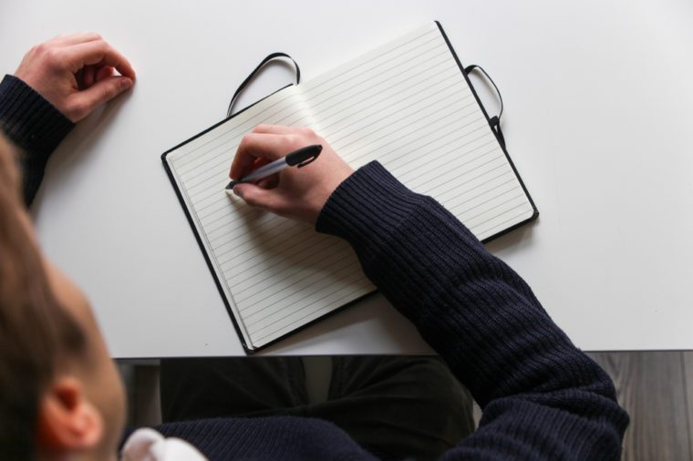 Student writes notes into notebook on white desk with black pen, top view
