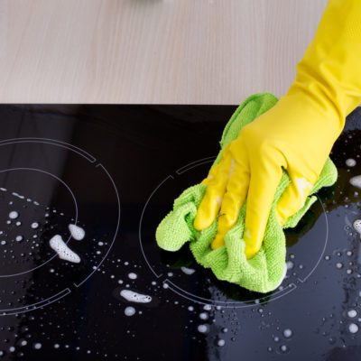 Close up of human hand with protective gloves cleaning induction hob with green mop