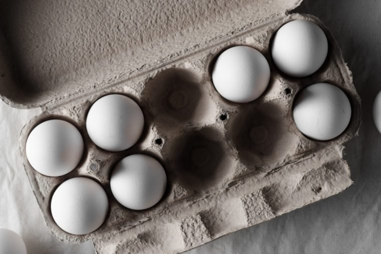 White eggs in an egg carton. White linen tablecloth background.