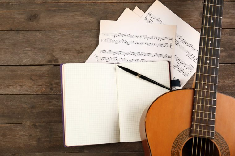 Music recording scene with guitar, notebook and music sheets on wooden table, closeup