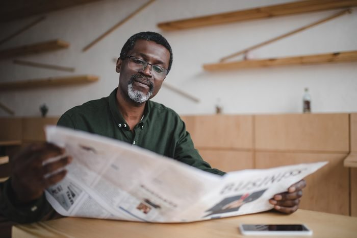 mature african american businessman reading newspaper in cafe