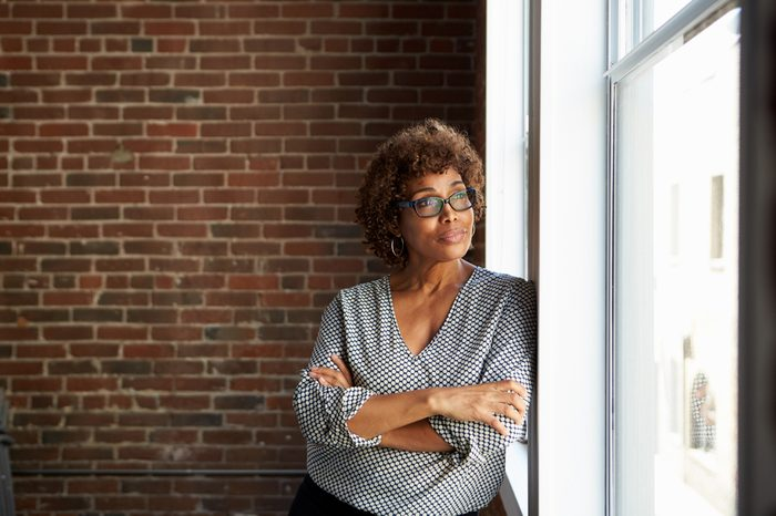 Mature Businesswoman Standing By Office Window