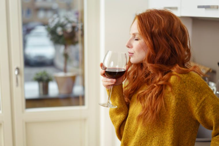 Young redhead woman standing in her apartment sipping a glass of red wine with her eyes closed in pleasure, side view