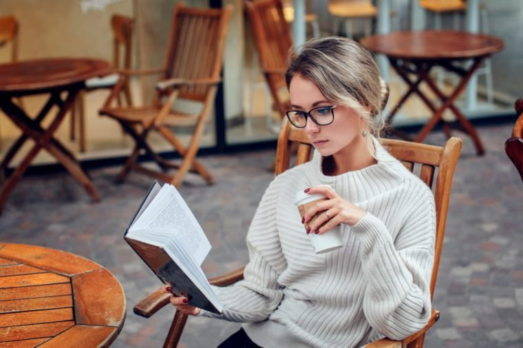 Beautiful young woman reading a book with a cup of coffee sitting in the street cafe