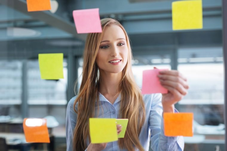 Business plan. Young female professional sticking colourful notes to a glass wall
