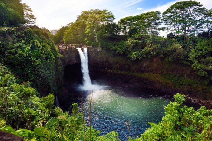 Majesitc Rainbow Falls waterfall in Hilo, Wailuku River State Park, Hawaii. The falls flows over a natural lava cave, the mythological home to Hina, an ancient Hawaiian goddess.